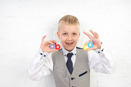 handsome boy holding small wooden letters in hands. white wall studio. conceptual idea about modern language education system. a guy dreams of his future profession, diligent student in school college