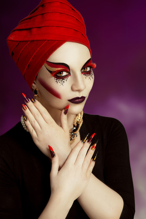 Woman plays a role, wear a mask, long lashes. White skin magic beautiful lady, professional model makeup, very long nails extension, full fashion look. Creative make-up made by professional cosmetics