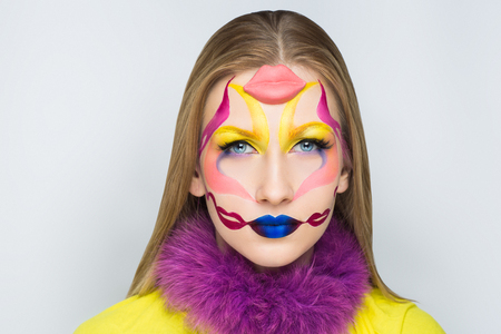Creative make-up new conceptual idea. blue lips yellow white bold body art painting. Crazy new graphic abstract picture on woman face surrealistic. Horizontal professional photo. Creativity background Stock Photo
