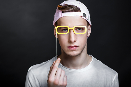 Paper eyeglasses hand made crafts, accessories cardboard attributes on sticks for a professional photo shoot. Young man holding vision in his arm. Expressing emotions of serious person love studying