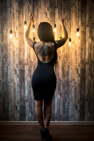 Sexy woman with perfect body, beautiful face. wooden wall, hanging light bulbs. Girl erotically arched back. Waiting for the return of men from work. Excitement, Passion. Professional photo big banner