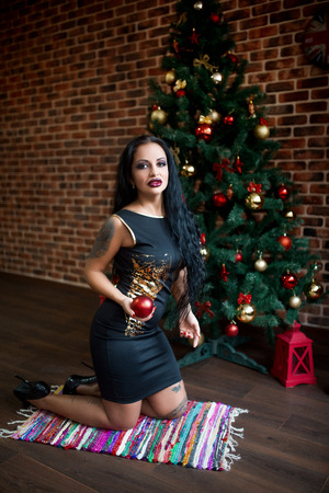 Sexy woman with perfect body, beautiful face. Girl kneeling on floor carpet erotically arched back. Waiting for return of men from work. Excitement Passion. New professional photo, big Christmas tree Stock Photo