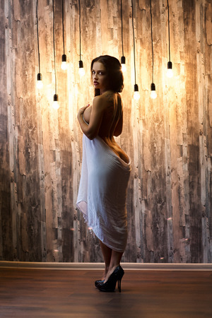 Vertical professional photo. Sexy woman with perfect body, beautiful face. Girl erotically arched back. Waiting for the return of men from work. Excitement, Passion. Hand cloth covers large breasts