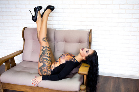 Vertical professional photo. Sexy woman with perfect body, beautiful face. Girl erotically arched back. Waiting for the return of men from work. Excitement, Passion. large breasts, snake tattoo on hip
