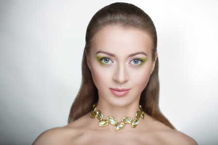 Young beautiful girl woman lady model fashionable hairdo professional makeup. Closeup photo face sexual necked shoulders. light gray background free place, shiny vip necklace, natural herbal cosmetics