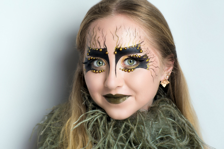 Woman with skin problems. Conceptual make up shows real skincare dermatology illness. Big accessory scarf with feather boa. Girl looks like living mermaid. makeup body art concept idea Halloween party Stock Photo
