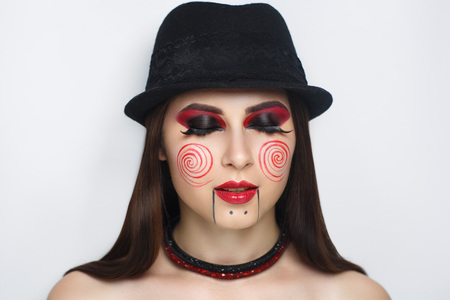 Scaring woman bodyart. Halloween make up Billy doll from horror movie film about saw. Red lips and round spiral painted on the cheeks. New crazy idea for faceart. Character who kill victims for fun