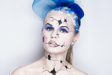 Art make up vintage porcelain doll with broken face black cracked pieces lines. Pink cheeks shadows blue eyes hair. New conceptual body art painting for halloween horror party night. Horizontal banner Stock Photo
