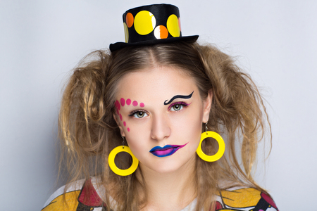 Young beautiful girl with a fashionable circus hat and professional makeup. Long big pink arrows eye cosmetics. Luxury jewelry yellow round earrings, small strange hat, Two sloppy tail of hair style