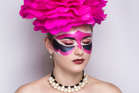 Beauty portrait of beautiful young woman girl lady model, red lips and big pink accessory. Professional makeup studio. New big carnival mask prepare for party masquerade in Brazil Italy Venice France Stock Photo