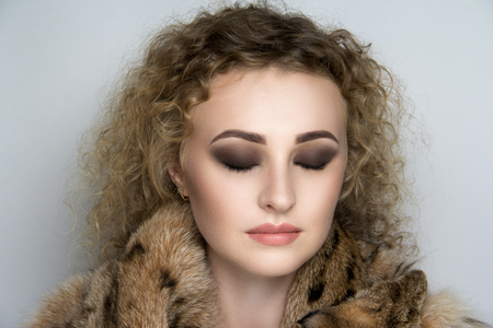 Close up portrait of beautiful curly woman pretty lady sexy girl young face. Fur coat vest skins lynx natural coloring, surround collar warm in winter from the cold. Clothing store, custom tailoring. Stock Photo