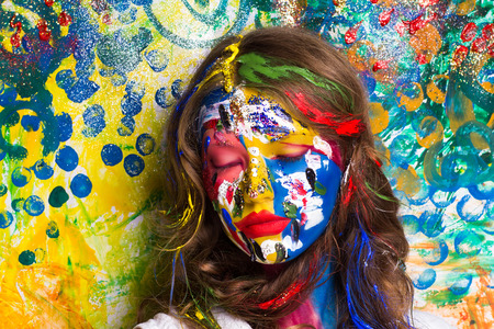 Creative make-up new conceptual idea. blue red yellow white bold body art painting. Crazy new graphic abstract picture on woman face surrealistic. Horizontal professional photo. Creativity background Stockfoto