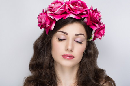 Charming girl with an angelic face and a beautiful accessories flower big pink roses wreath tiara. Pretty young lady pink lips perfect shape brown eyebrows eyes make up skin texture shadows. Happiness