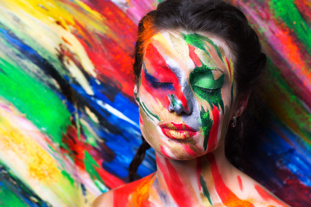 Creative make-up new conceptual idea. blue red yellow green bold body art painting. Crazy graphic abstract picture lines on woman face surrealistic. concept professional photo. Creativity background