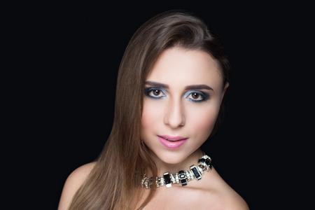 ファッショナブルなヘアスタイルとプロのメイクの美しい少女。黒銀の目の影、完璧な形の眉が柔らかく光沢のある唇の色の口紅。高級アクセサリ