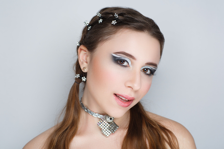 Young beautiful girl with a fashionable hairdo and professional makeup. Long braided healthy hair combed by brush. Luxury jewelry big necklace with natural stones treasure. Necked sexy body shoulders