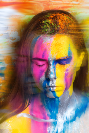 Creative make-up new conceptual idea. blue orange yellow silver bold body art painting. Crazy new graphic abstract picture on woman face surrealistic. concept professional photo. Creativity background