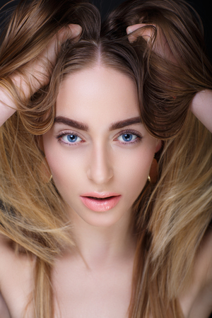 Woman is sexually breathing. Closeup portrait beautiful girl lady, volume messy hair styling. Bright makeup peach colour, tender lip-gloss new lipstick. Professional photo model person