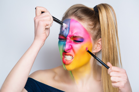 Girl painter holds black artist professional brush, all body Painted in gouache watercolor acrylic oil paints. Creative makeup new conceptual idea. Crazy new graphic abstract picture woman face lines Stock Photo - 90865284