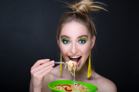Beautiful woman is eating a salad of cabbage and red bell pepper. Bright green fashionable make up eye shadows, long yellow earrings. banner conceptual idea healthy food diet. Creative devour mouth Stock Photo