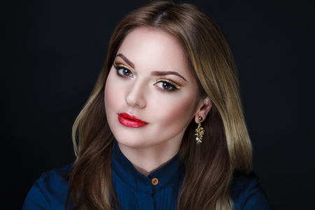Beautiful woman lady model wears fashionable formal blue blouse, golden earrings. Bright golden long wavy hair. beauty girl face professional makeup. Portrait closeup, clever eyes thinking dreaming