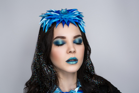 Young beautiful bright showy girl lady model snow queen. Fairy tale future party disco club. new Art makeup flawless face blue accessory, brown brunette hairdo eyebrows bright lips. Facial, horizontal Stock Photo