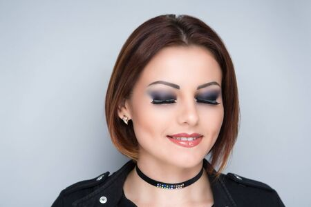 Portrait of beautiful girl woman face closeup, combed hair styling. Luxury professional makeup. Bright shiny lip-gloss lipstick. Sexy black jacket shoulders. New Horizontal photo gray dark background
