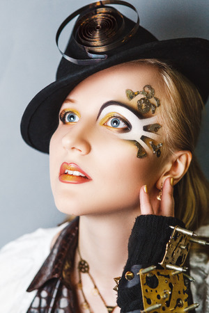 Woman steam punk make-up. Girl decorated with gears from the clock. Creative idea. colorful bold face-art painting lines shadows. graphic abstract picture woman face. Conceptual post-apocalypse style