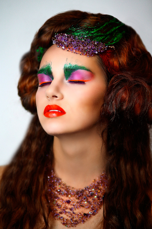 Woman with Creative green brows orange lips make-up, conceptual idea for Halloween. volume hair dress, body art painting. Professional photo free background vertical. beads decoration on head and neck