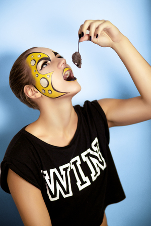Creative make-up new conceptual idea. yellow white bold art painting. Crazy graphic abstract picture woman face surrealistic. professional photo. Creativity pop art, lines shadows, long black nails Archivio Fotografico