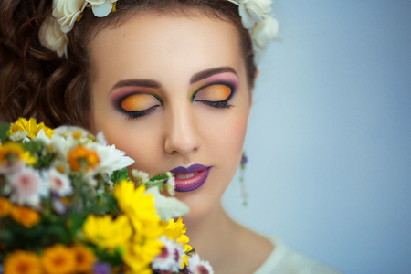 Pretty girl sniffing flowers bouquet. Creative young lady bright makeup, diadem tiara. Streams of flowers, shiny cheek colored big eyes pink ultra mat lips. Professional photo new stylish florist idea Stock Photo