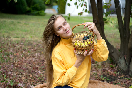 Beautiful woman relax in the garden, sits on a wool blanket. beauty of nature, autumn park. Round shape wicker basket, daylight illuminates plants. picnic in the village, fresh air. horizontal banner