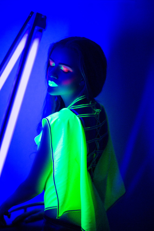 Creative woman lady girl model shine with blue green orange colors. Bright conceptual art make-up glows under ultraviolet light. Club disco neon party time. Drink alcohol feel wild energy of music