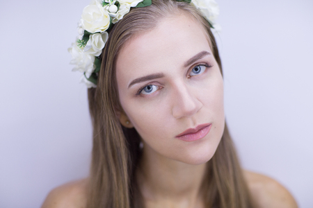 Young beautiful girl woman lady female with fashionable tiara flowers wreath and professional makeup. Long blonde straight hair, arrows beige eye shadows, natural nude lipstick gloss. Luxury accessory