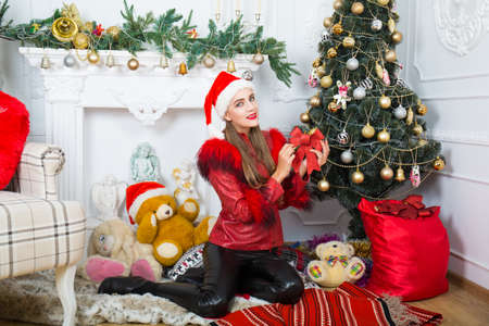 Beautiful woman near x-mas tree, happy New Year party  Santa girl, dreaming about presents and surprises