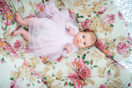 Beautiful baby girl lying rolling over in bed, pillow cover carpet. emotional pretty kid lovely princess in pink dress. lie on back. horizontal photo, background flowers. sweet family love concept