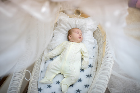 Beautiful baby girl lying sleeping in big ivory bed, pillow cover. pretty kid lovely princess in yellow dress overalls sliders. lie on back. horizontal photo. sweet family love concept, reach luxury Stock Photo