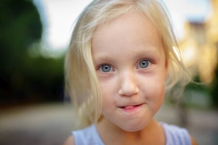 Little beautiful girl with clear blue eyes. A cunning expression. The tongue thrusts out. Light blonde hair. Horizontal banner, social problem all kids needs parents love, live in family with mom dad