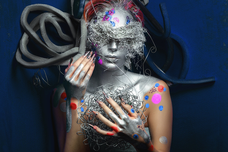 Young beautiful bright showy girl lady model robotic queen. Fairy tale future party disco techno club. new art makeup flawless face silver dark eyes cheeks matte lips. Facial painting, very long nails