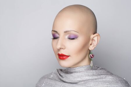 Close up portrait of beautiful bald woman. Perfect beige skin, sexual naked closeup. Sexy passionate girl with informal strange appearance. Challenging society, cut hair. Gray background free place