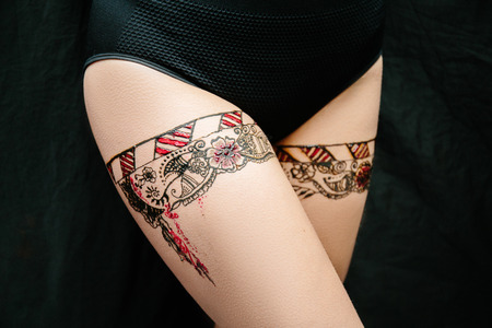 Drawing mehendi on white skin woman legs. Shapely hips with vintage linens. Black red picture abstract flowers flame. henna painting design for wedding party. Close up professional photo