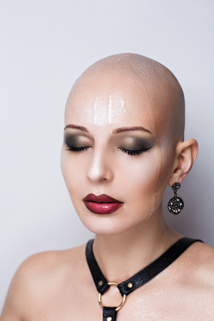 Close up portrait of beautiful bald woman. Wet skin, drops of water or of tears running down her face, shoulders