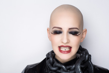 Close up portrait beautiful bald woman. Perfect beige tone skin face, professional makeup, black leather shoulders big chain. Sexy passionate girl with informal strange appearance. Challenge cut hair