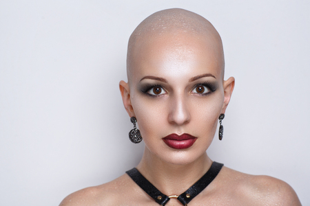 Close up portrait of beautiful bald woman. Wet skin, drops of water or of tears running down her face, shoulders. Sexy passionate girl with informal strange appearance. Challenging society, cut hair