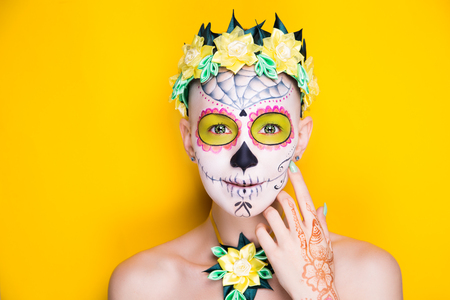 New creative make up of funny human sugar skull. applied to face-art Mexican celebration, Day of the Dead Dia de los Muertos, Roman Catholic holiday All Souls Day. Yellow horizontal banner free place