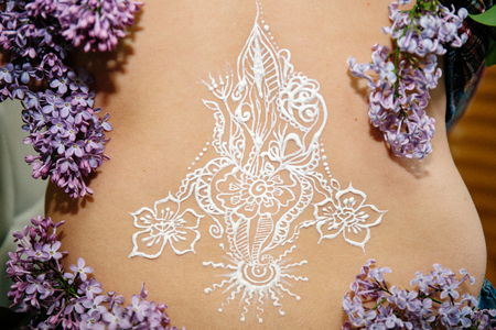 Drawing mehendi on white skin woman back. White picture abstract flowers sun flame. White henna painting design for wedding party. Middle lumbar spine.  branches of lilac. Close up professional photo  Reklamní fotografie