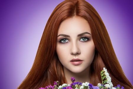 Bright orange brown long straight hair. Oriental beauty girl professional makeup. Portrait beautiful woman lady nymph holding flowers smell bouquet. Young gypsy fortune teller predicts fate horoscope Foto de archivo