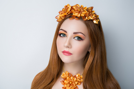 Bright orange brown long straight hair. Oriental beauty girl professional makeup. Portrait of a beautiful woman who wore big gold flower wreath accessory. Young fortune teller predicts fate horoscope