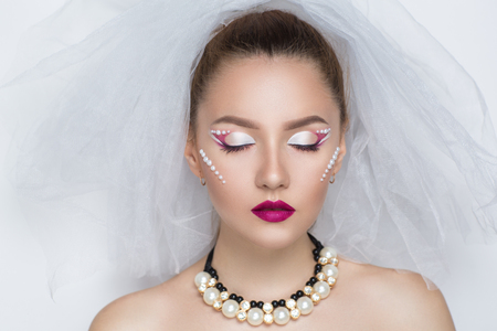 Beautiful bride woman girl lady princess prepare for wedding - white long veil, silver diamond earrings, necklace. Professional make up bright eyes, red pink lipstick. background free place