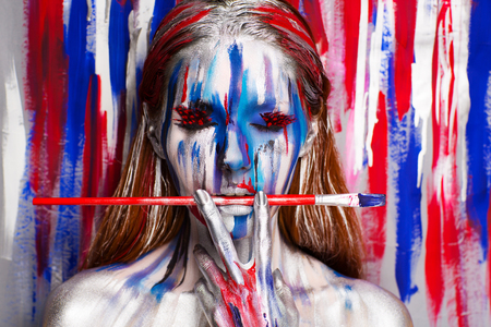 Girl painter with big artist professional red brush, all body Painted in gouache watercolor acrylic oil paints. Creative makeup new conceptual idea. Crazy new graphic abstract picture woman face lines Stock Photo - 92809890
